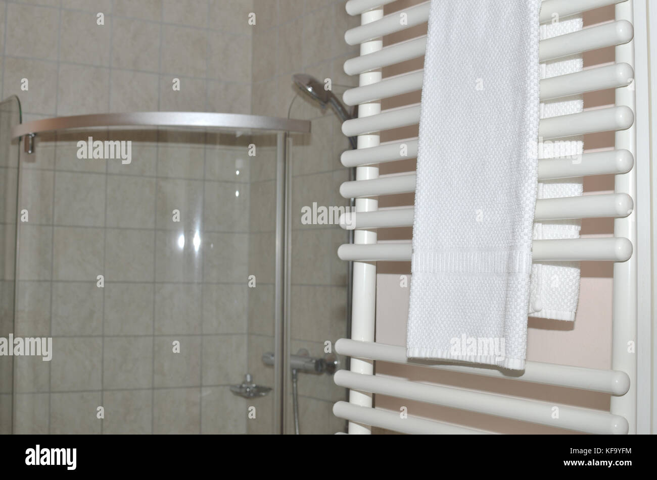 Beau Towel Dryer With White Towels In A Bathroom And A Shower Cabin Behind
