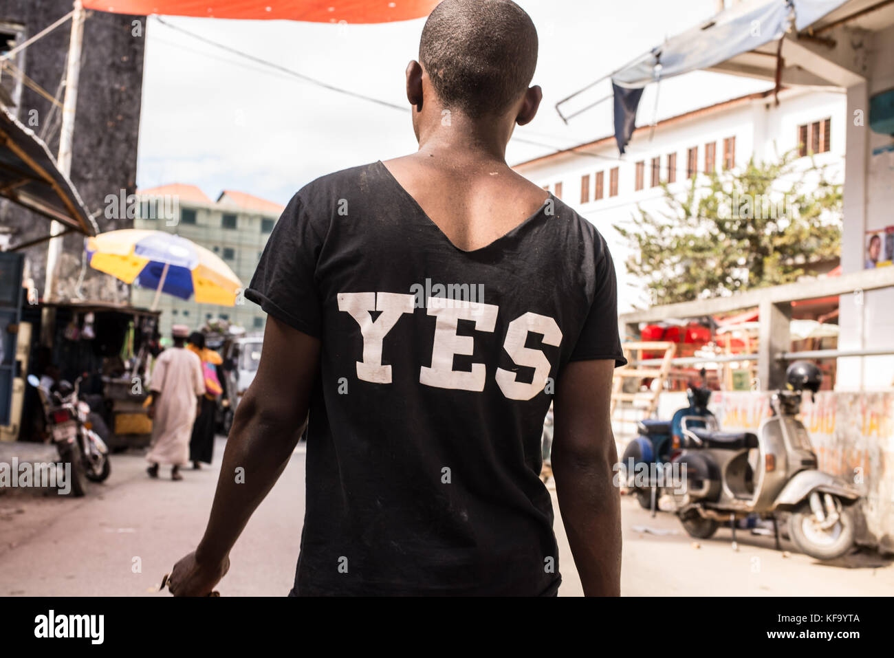 African man walking on a market street photographed from behind wearing a black T-shirt with YES written in white - Stock Image