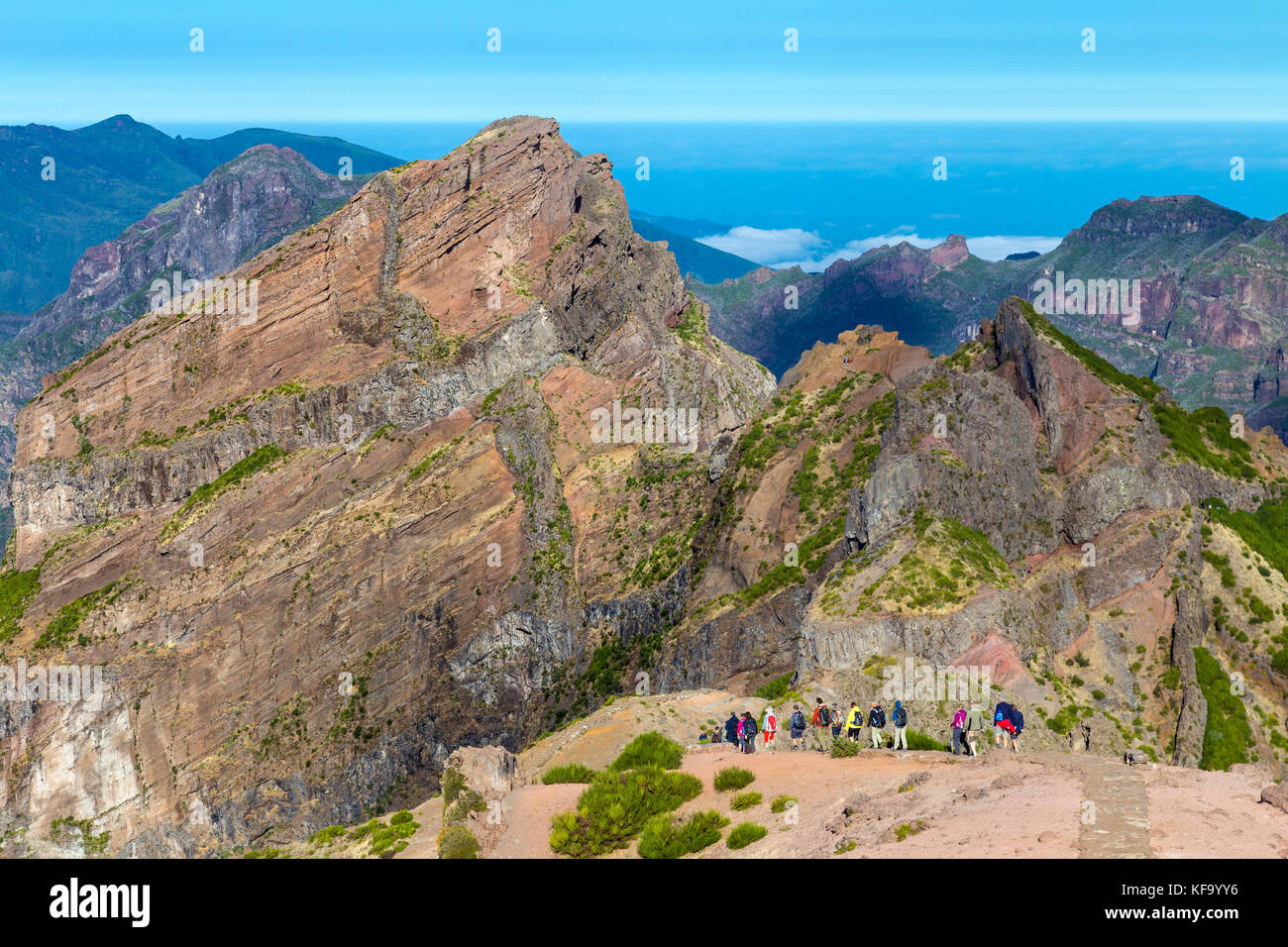 Group of hikers taking off from Pico do Ariero to climb the summit of Pico Ruivo in Madeira, Portugal - Stock Image