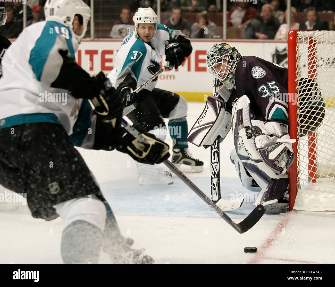 San Jose Sharks' Joe Thornton, left, tries to pass the puck to teammate Grant Stevenson, center, as Anaheim - Stock Image