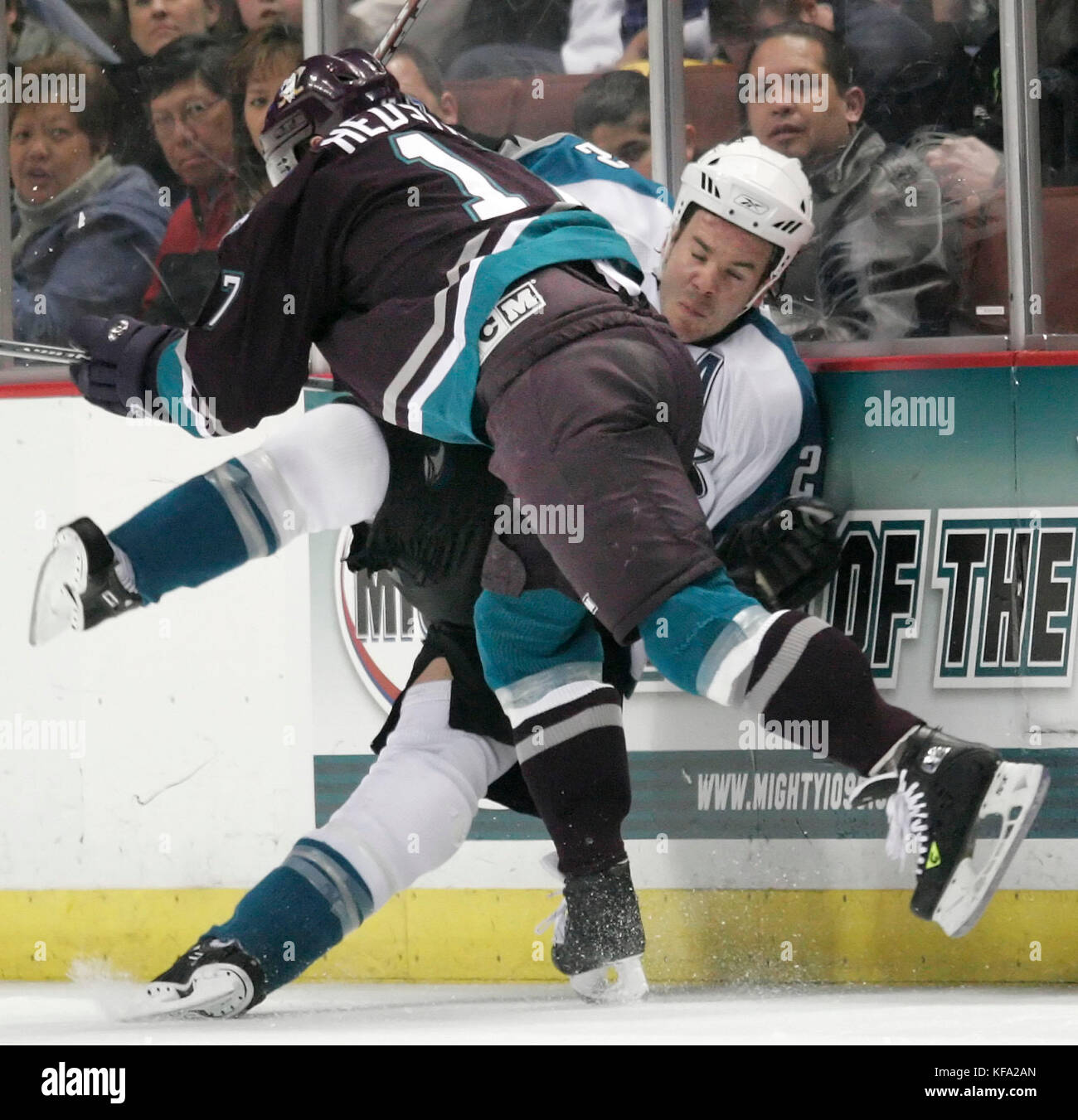 Anaheim Mighty Ducks' Jonathan Hedstrom of Sweden, foreground, checks San Jose Sharks' Scott Hannan into - Stock Image