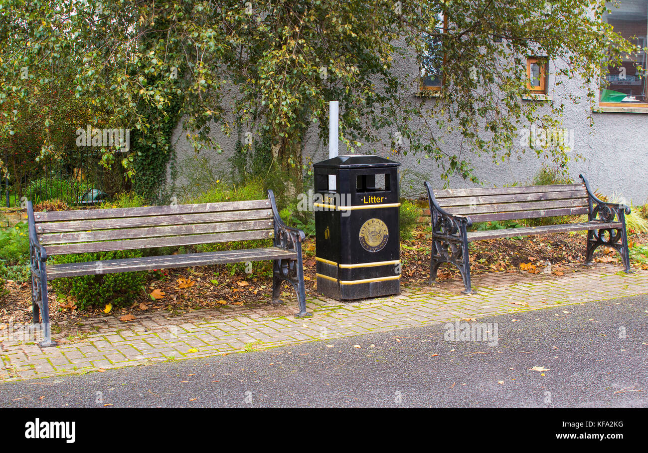 A pair of dilapidated park benches and a city council litter bin on the roadside in the small mill village of Edenderry - Stock Image