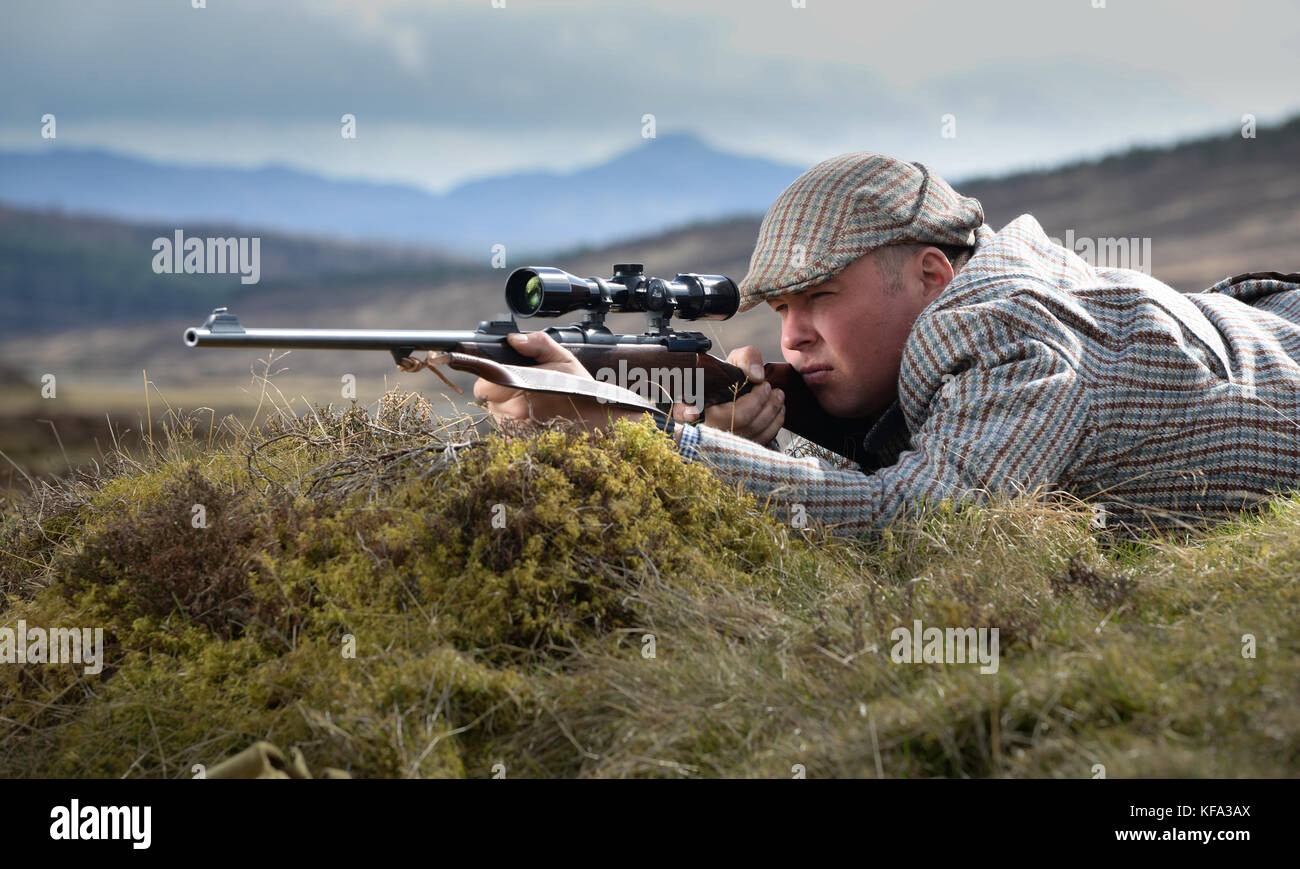 Deer stalker aiming rifle with telescopic sight - Stock Image