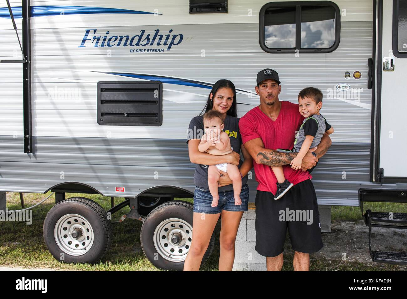 A family poses outside of their FEMA Travel Trailer during relief efforts in the aftermath of Hurricane Irma October - Stock Image