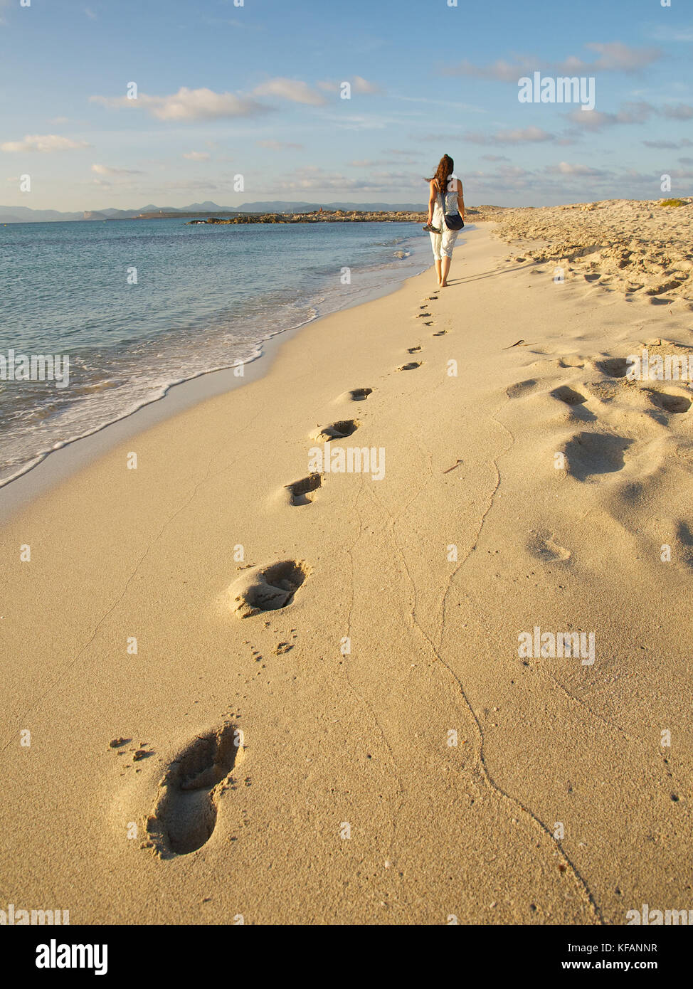 Woman walking by the sea leaving her footprints in the seashore sand at Ses Illetes beach, Formentera (Balearic - Stock Image
