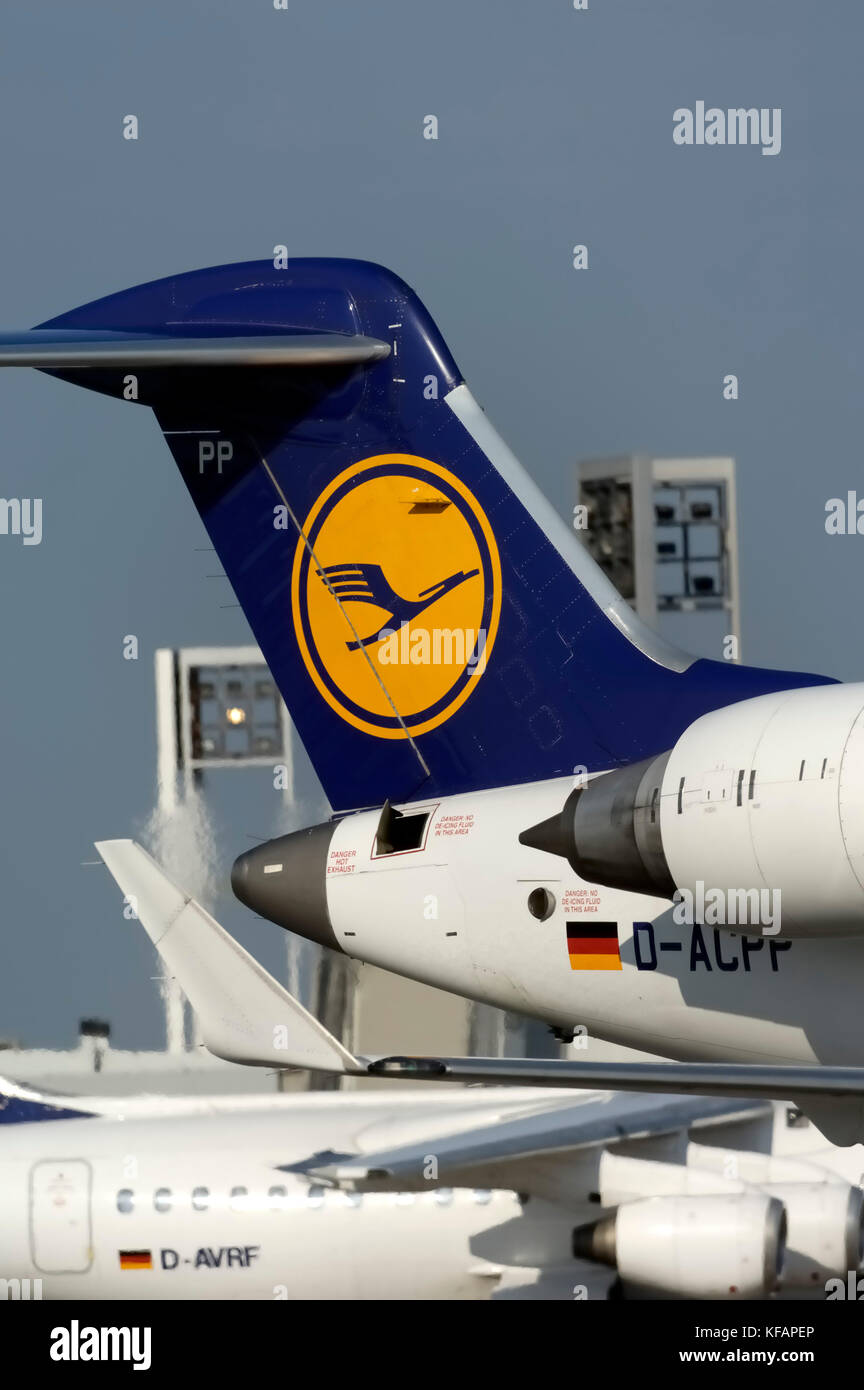 CRJ tail with logo, winglets and engines passing Terminal1 with a Lufthansa BAE 146 RJ-85 behind - Stock Image