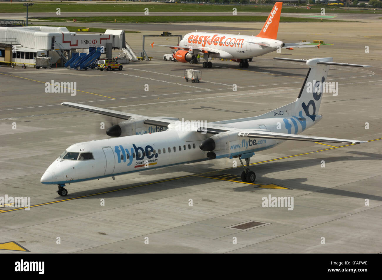 a Flybe Bombardier DHC-8 Dash 8-400 Q400 taxiing with an easyJet Airbus A319-100 parked behind - Stock Image