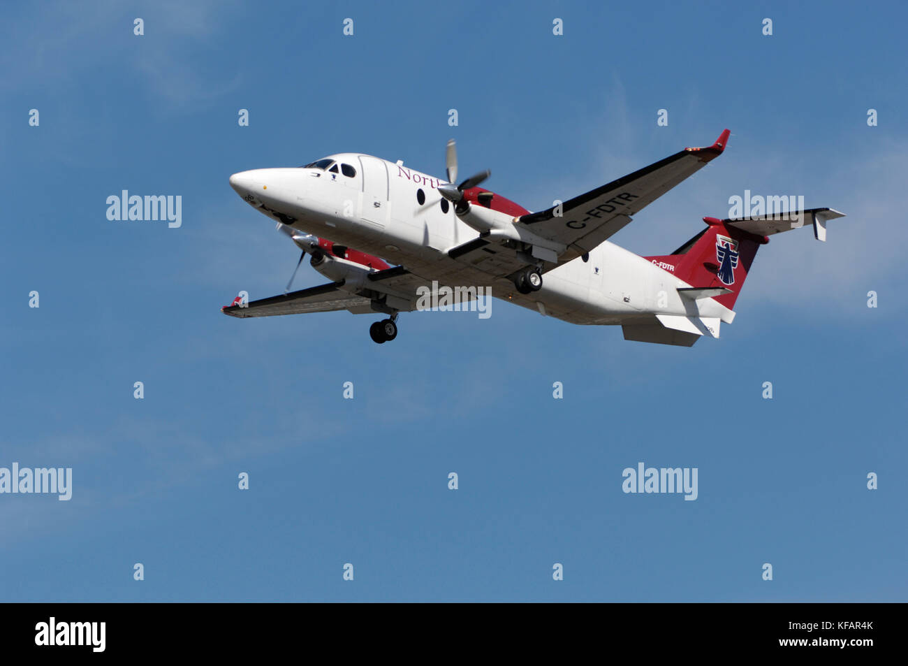 a Northern Thunderbird Air Beechcraft 1900D climbing after take-off with undercarriage retracting - Stock Image