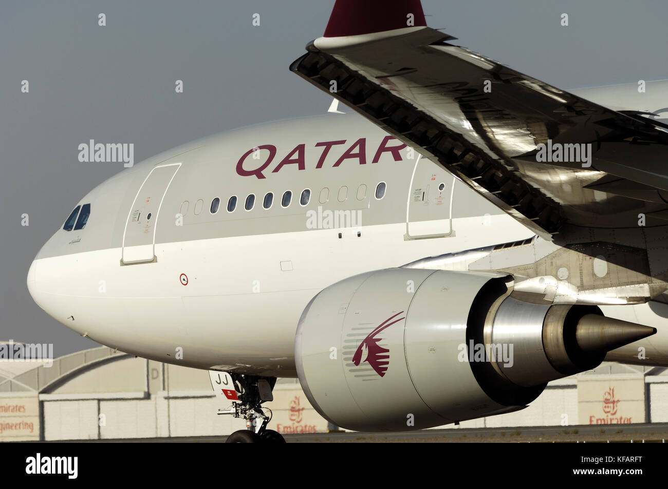 wing, engine and forward fuselage of a Qatar Airways Airbus A330-200 taxiing - Stock Image