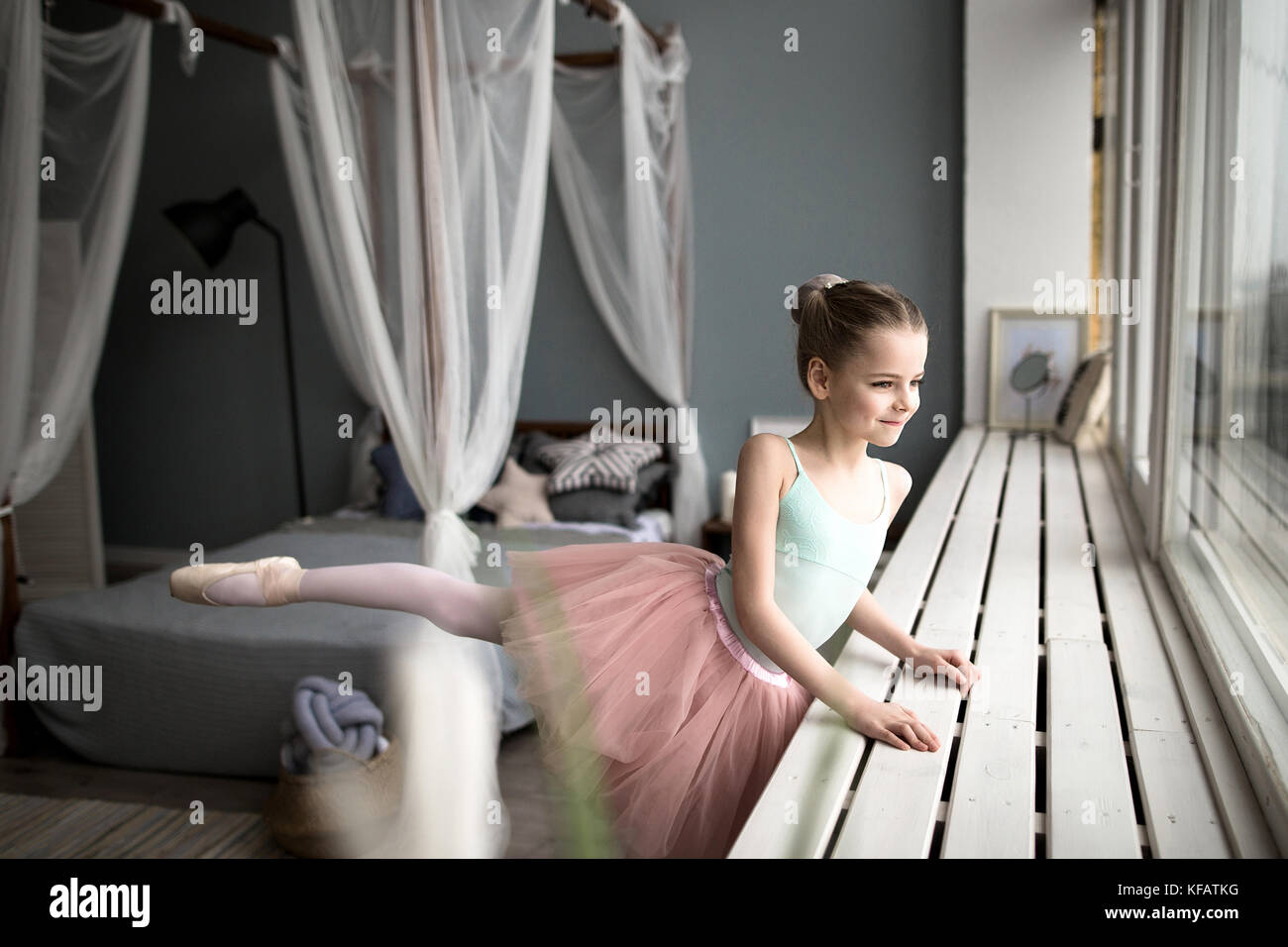 Cute little ballerina in pink ballet costume and pointe shoes is dancing in the room. Child girl is studying ballet. - Stock Image