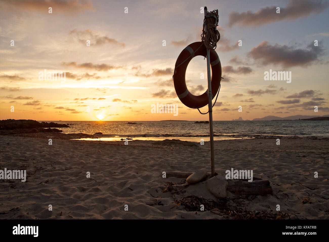 Lifesaver at sunset at Es Pas beach with Espalmador, Es Vedrá and Ibiza islands in the back at Ses Salines - Stock Image
