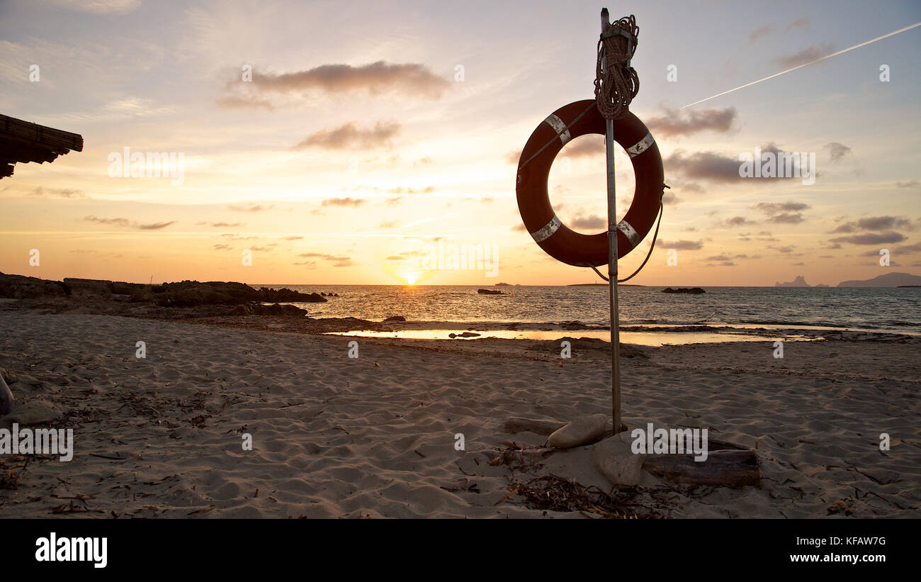 Lifesaver and plane trail at sunset with Es Vedrá and Ibiza islands in the back at Ses Salines Natural Park - Stock Image