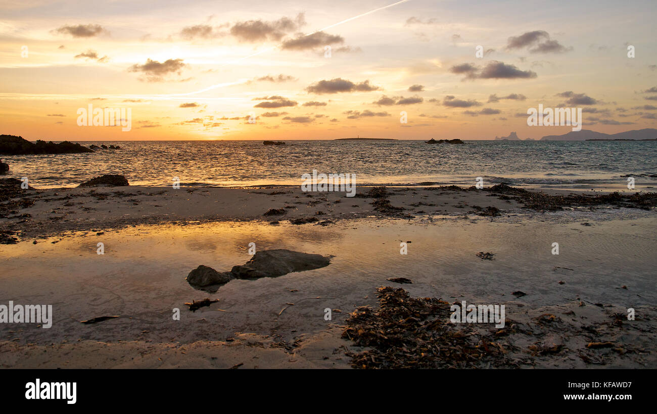 Sunset at Es Pas seashore beach with Es Vedrá and Ibiza islands in the background at Ses Salines Natural Park - Stock Image