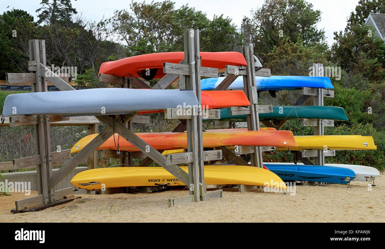 Colorful kayaks stored on wooden racks at Paine's Creek Beach and Landing in Brewster, Massachusetts, on Cape Cod Stock Photo