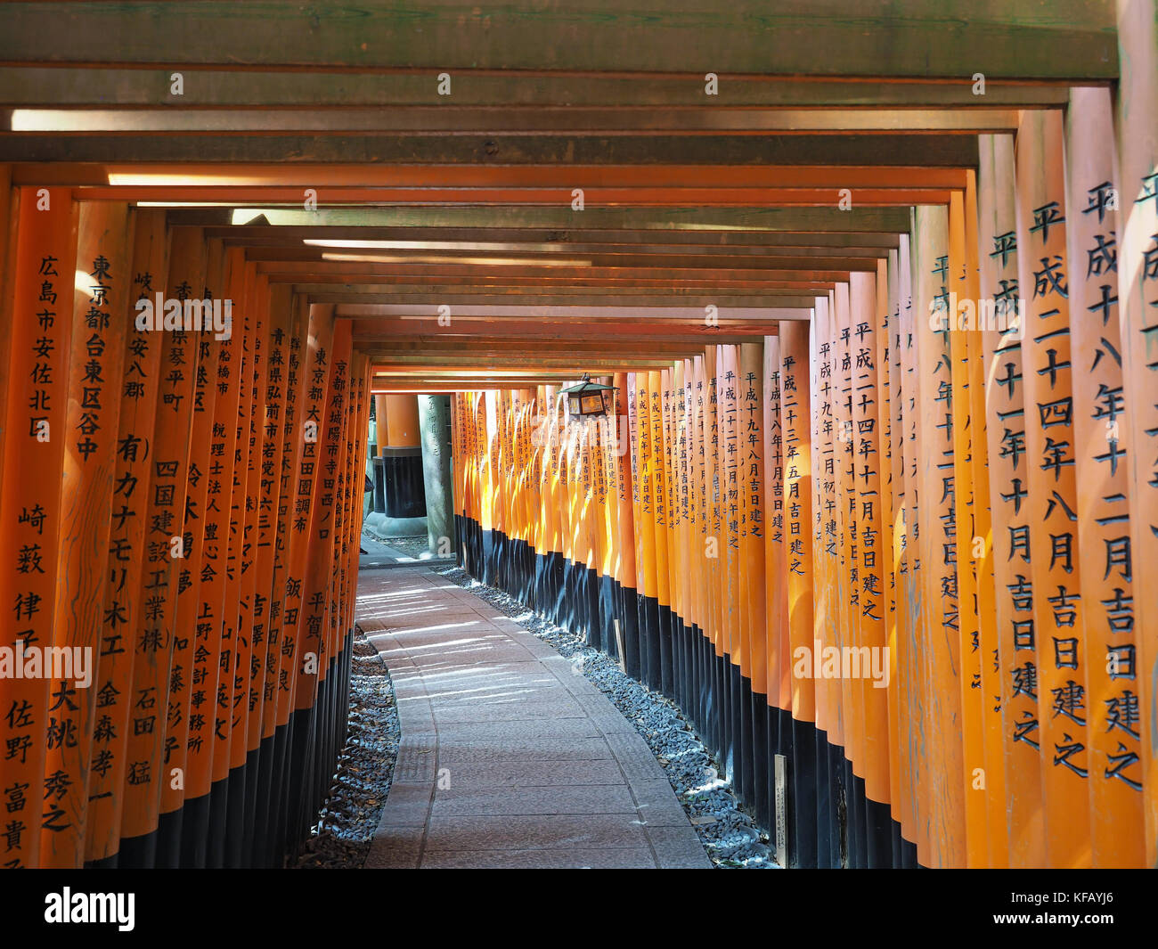 View looking along a tunnel of vermilion coloured torii gates at the Fushimi Inari Shrine in Kyoto Japan Stock Photo
