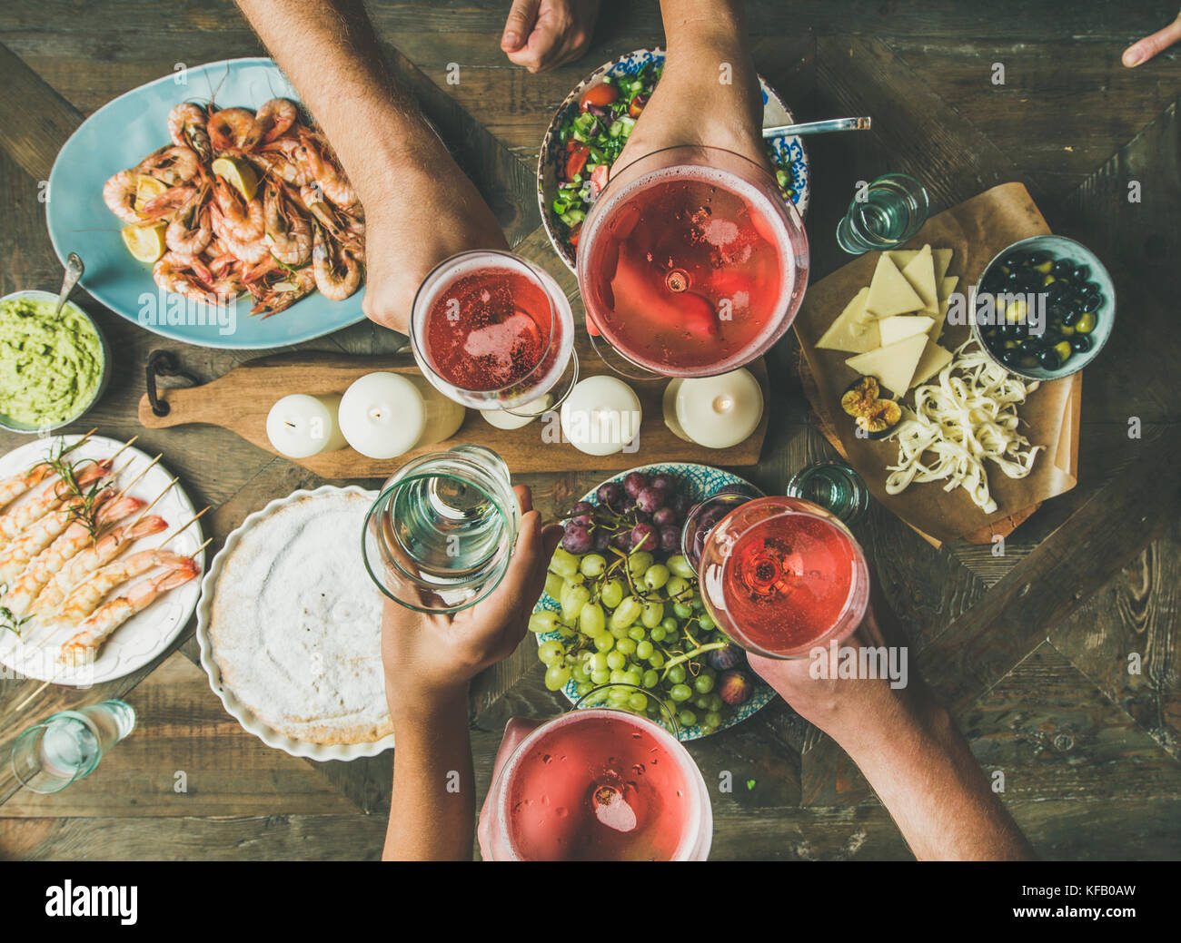 Holiday celebration table setting with food. Flat-lay of friends hands eating and drinking together. Top view of - Stock Image