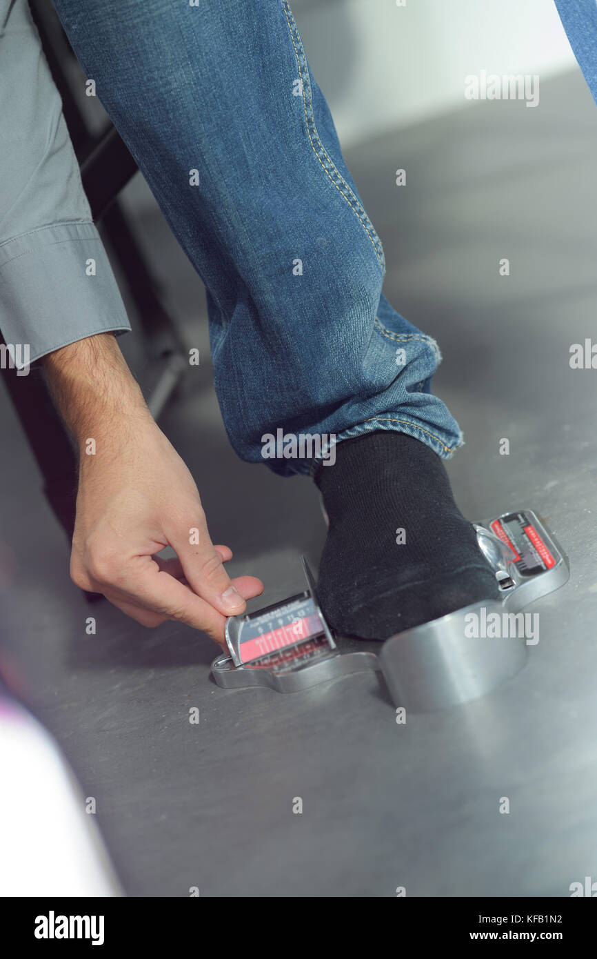 man measuring his feet Stock Photo: 164355998