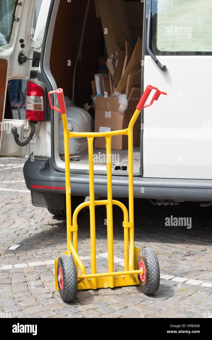Empty trolly near the open car on the street - Stock Image