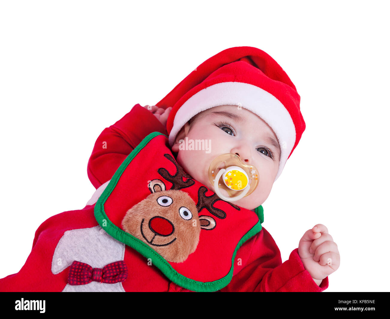 Baby girl with pacifier or dummy, red babygrow or onesie, Rudolph reindeer bib, Santa Claus hat for Christmas. Isolated - Stock Image
