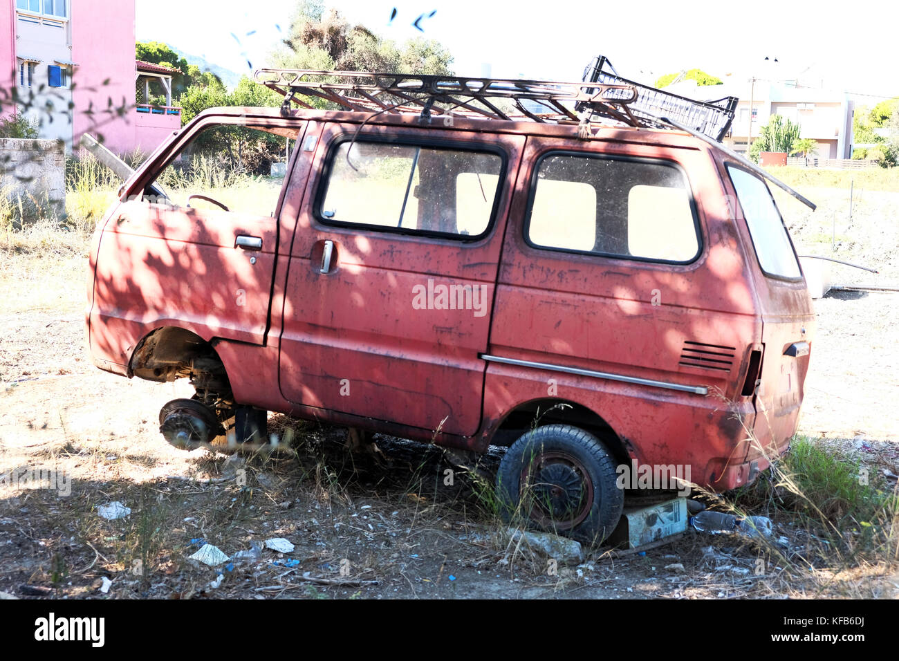 A battered neglected and abandoned people carrier van lies rusting away in a field impacting on the environment - Stock Image