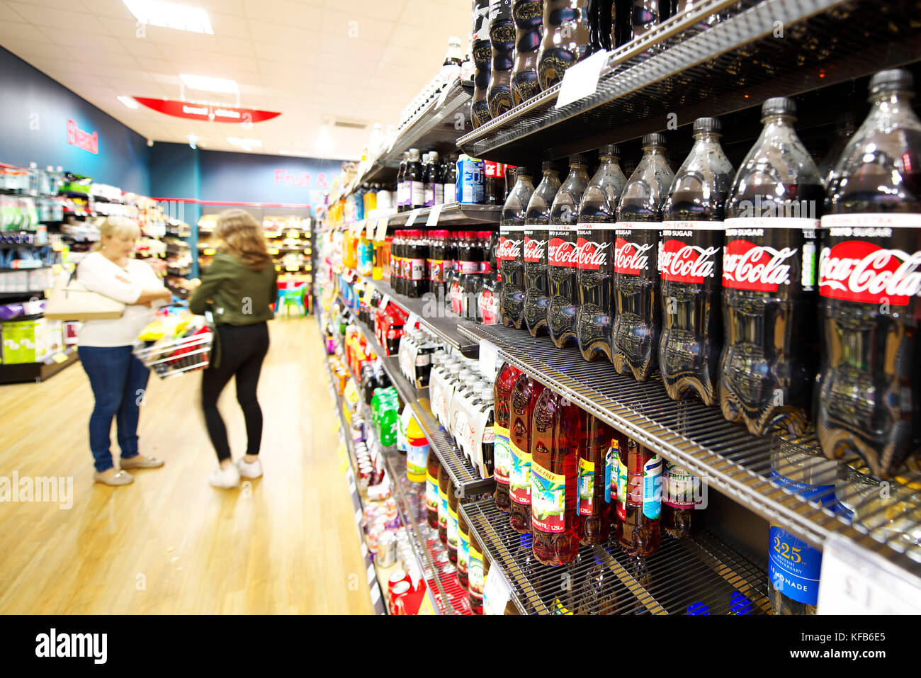 Shelves full of fat fizzy and zero sugar fizzy drinks for children and adults. Coca Cola in frame - Stock Image