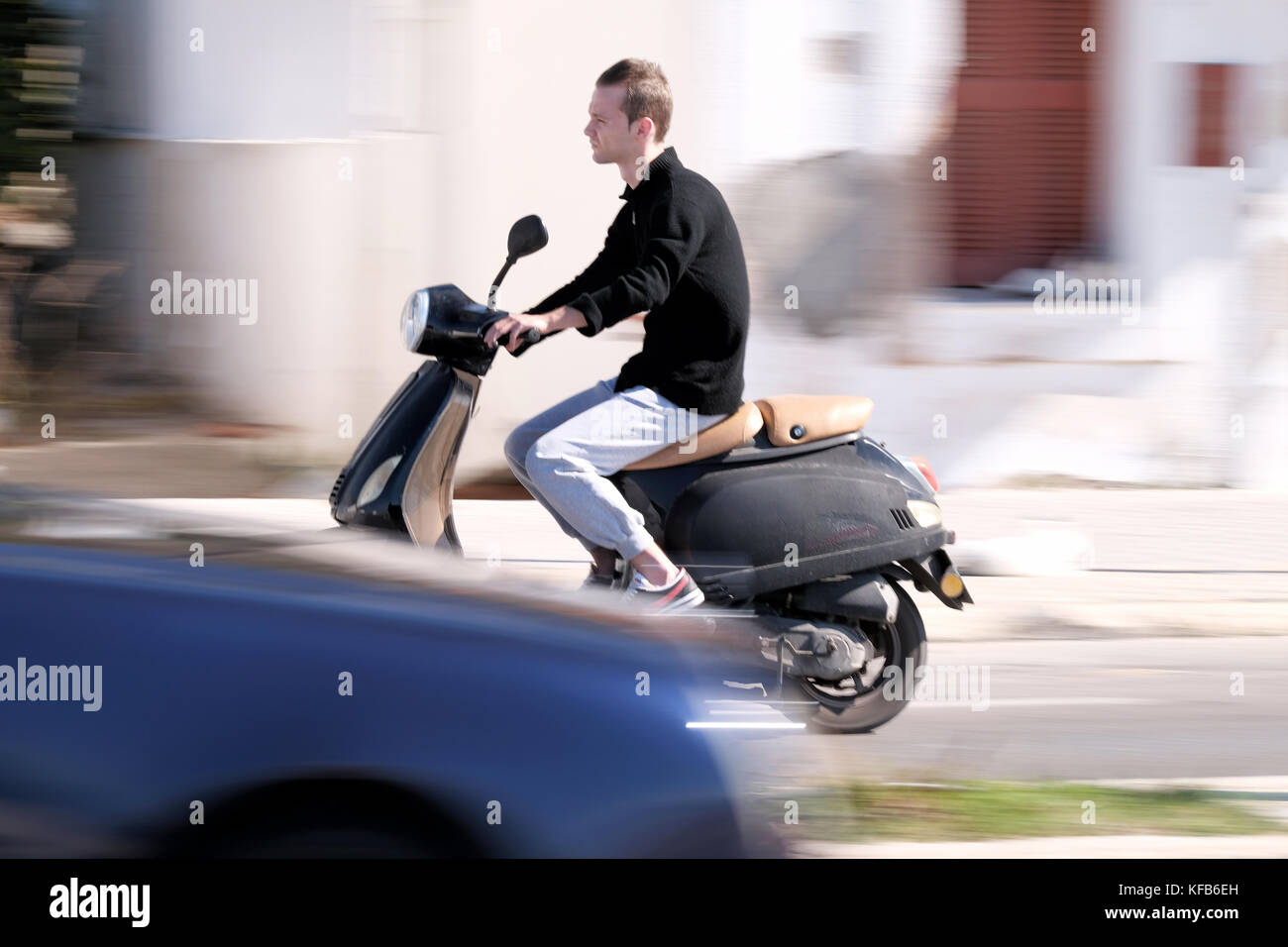 A youth riding a scooter at speed along the road. The shot is panned giving an impression of movement. Taken near - Stock Image