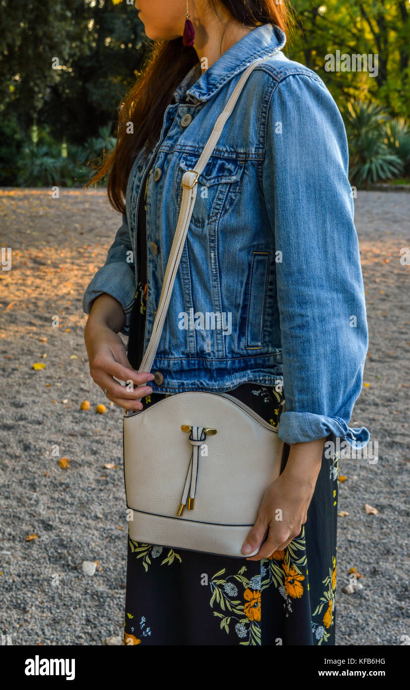 A young woman in a park, casually dressed, wearing a floral dress and a denim jacket, with a mini bag over her shoulder - Stock Image
