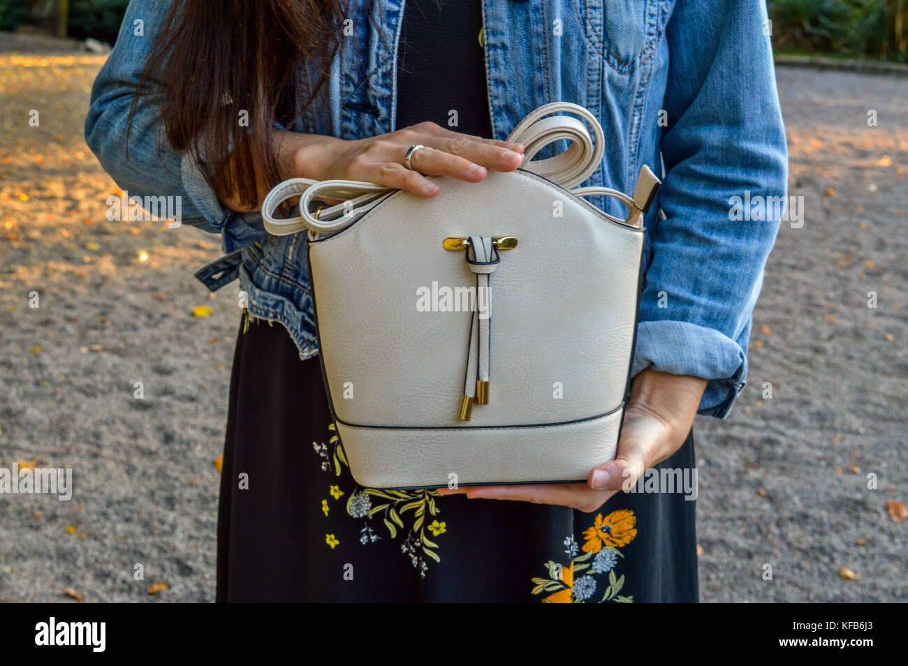 A young woman, casually dressed, wearing a floral dress and a denim jacket, holding a mini bag - Stock Image