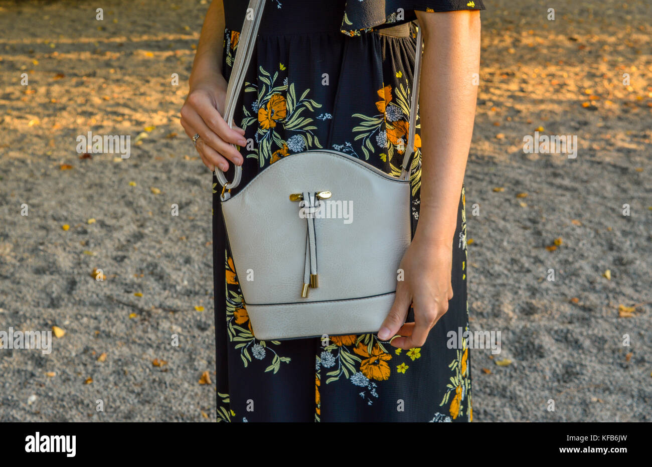 A young woman, wearing a floral dress, holding a mini bag - Stock Image