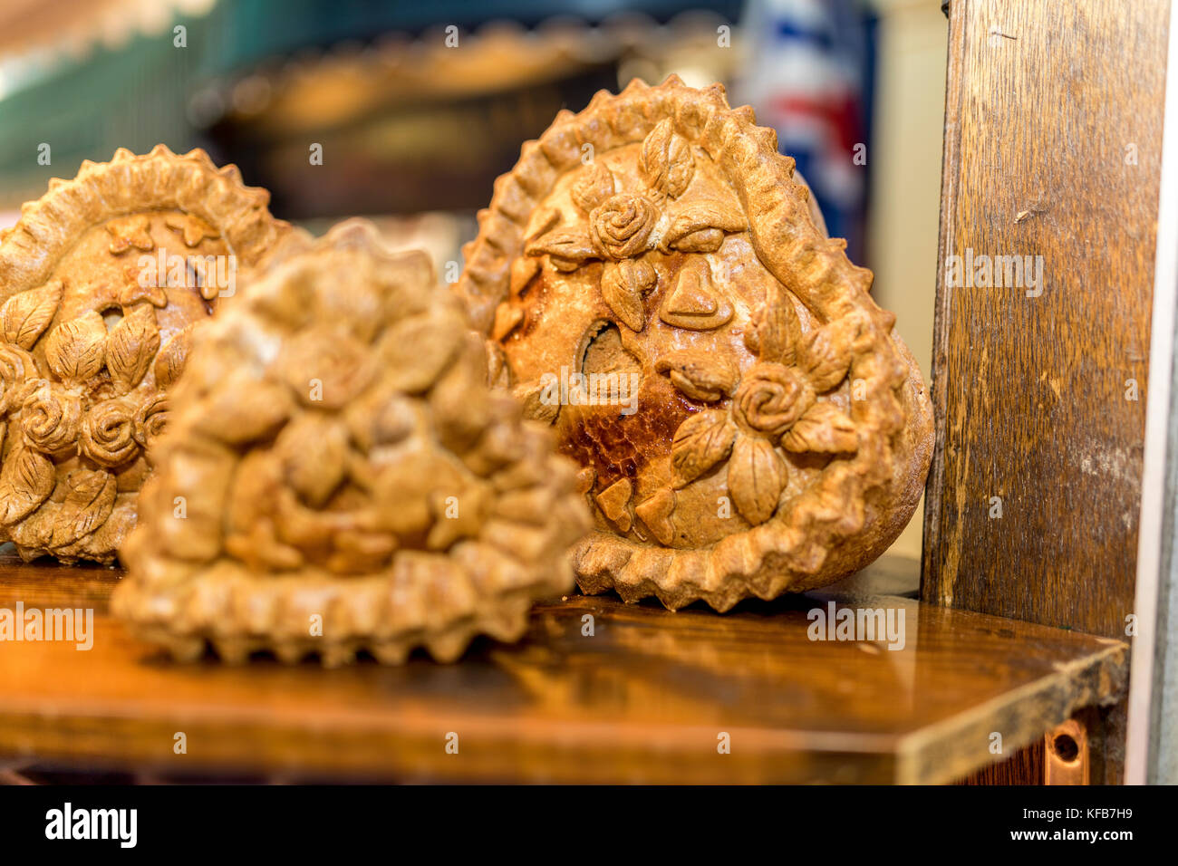Prize winning pork pie display with beautiful ornate crusty pastry featuring floral and rose flower patterns on - Stock Image