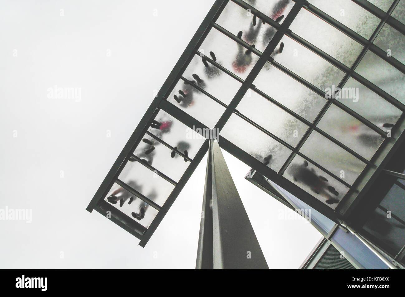 People standing over transparent floor, image taken from below - Stock Image