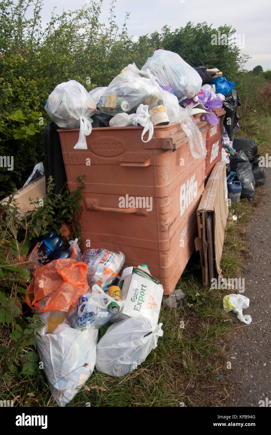 overflowing bin of rubbish dumped by narrow boat users at Cooks Wharf car park nr Cheddington, Buckinghamshire - Stock Image