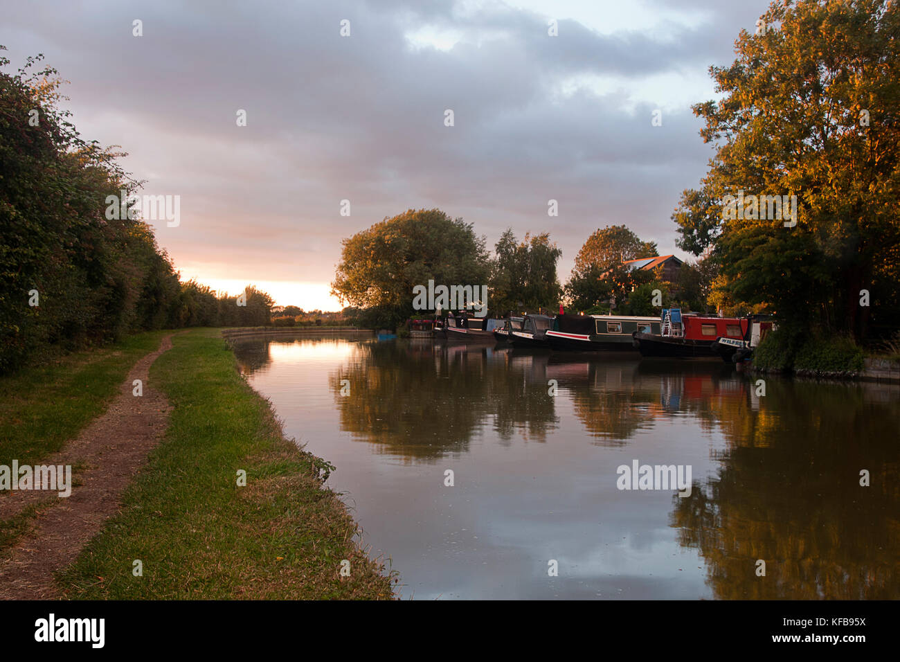 narrowboats and towpath along Cooks Wharf at sunset, Grand Union Canal Outer Aylesbury Ring, Cheddington, Buckinghamshire, Stock Photo
