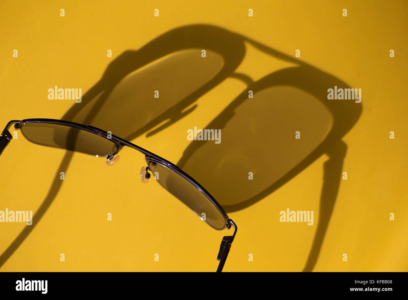 Abstract view of shadows cast by sunlight on a yellow background of a pair of eyeglasses - Stock Image