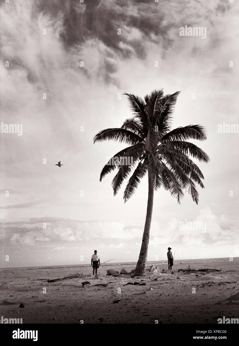 FIJI, Northern Lau Islands, a father and son wander across a small remote island to go fishing (B&W) - Stock Image