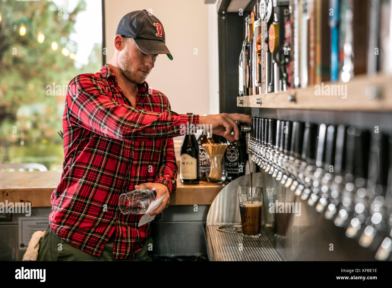 USA, Oregon, Bend, Pacific Pizza and Brew, bartender pouring pint - Stock Image