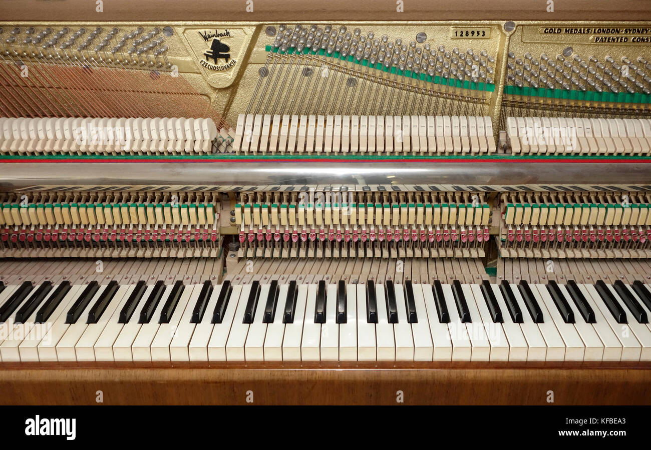 Upright piano stripped from upper front doors and fall showing keyboard and action mechanism & Upright piano stripped from upper front doors and fall showing Stock ...