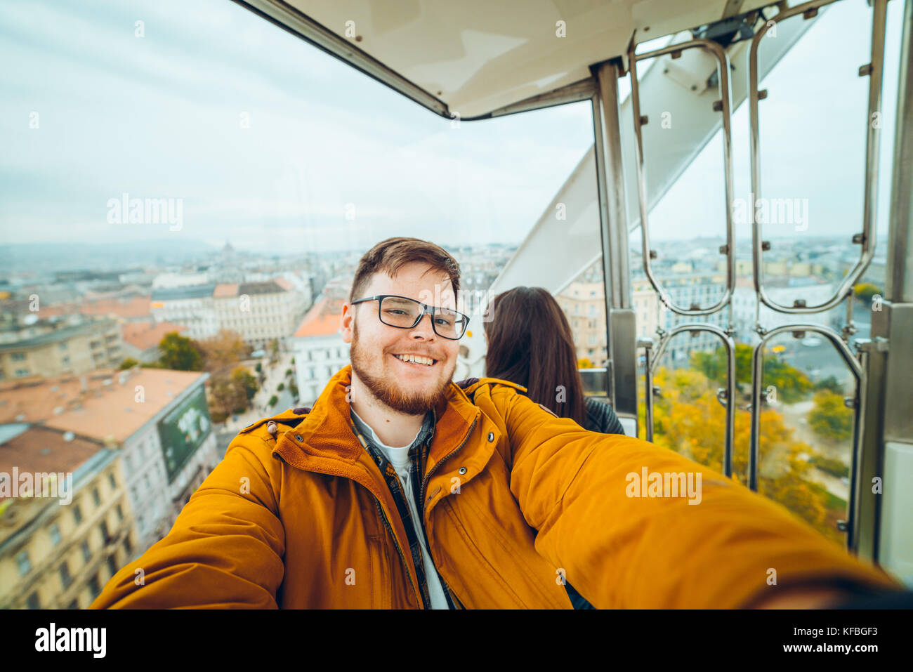 man with woman at ferris wheel taking a selfie - Stock Image
