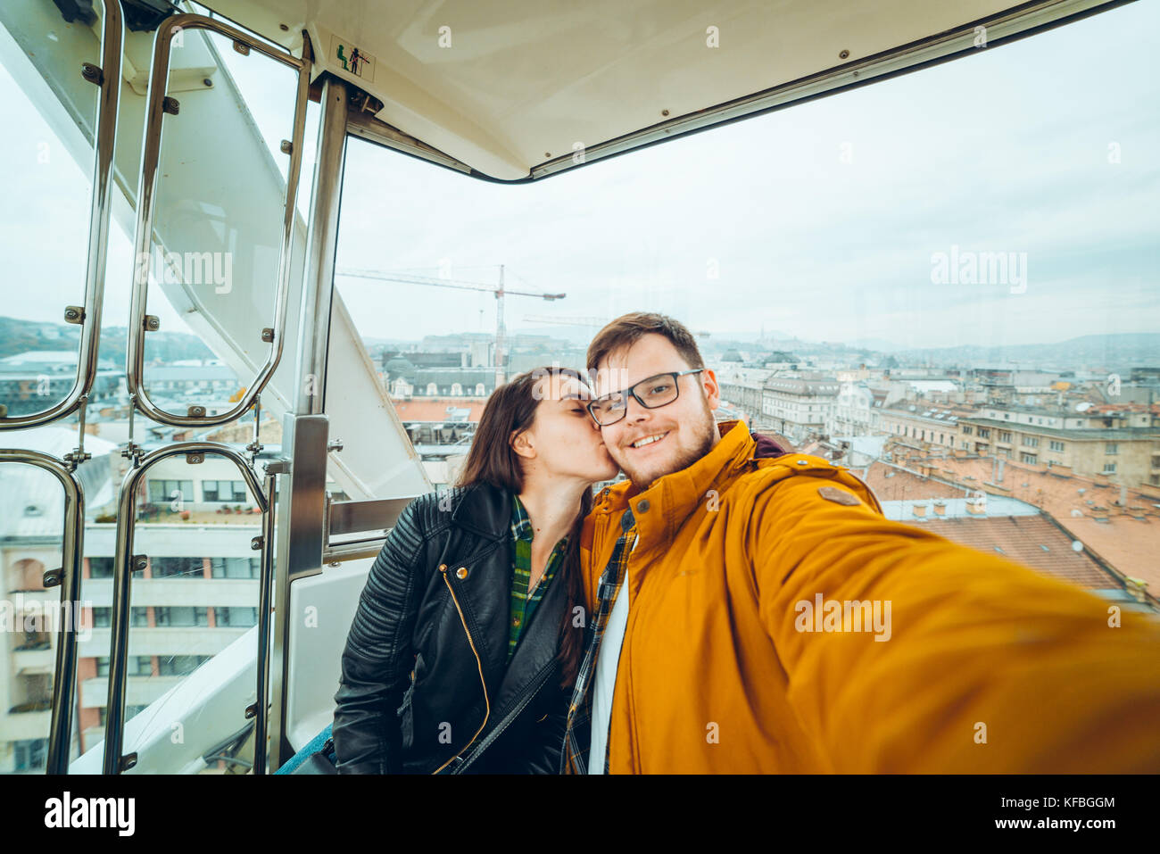 man with woman at ferris wheel taking a selfie Stock Photo
