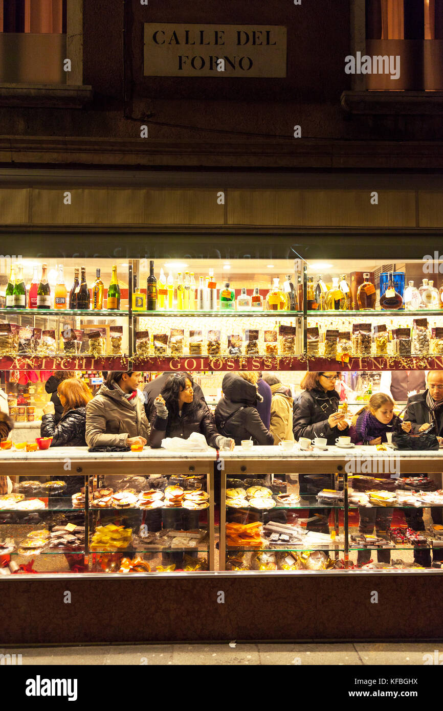 ITALY, Venice. Patrons at a shop enjoying Pastries and drinks at night. Stock Photo