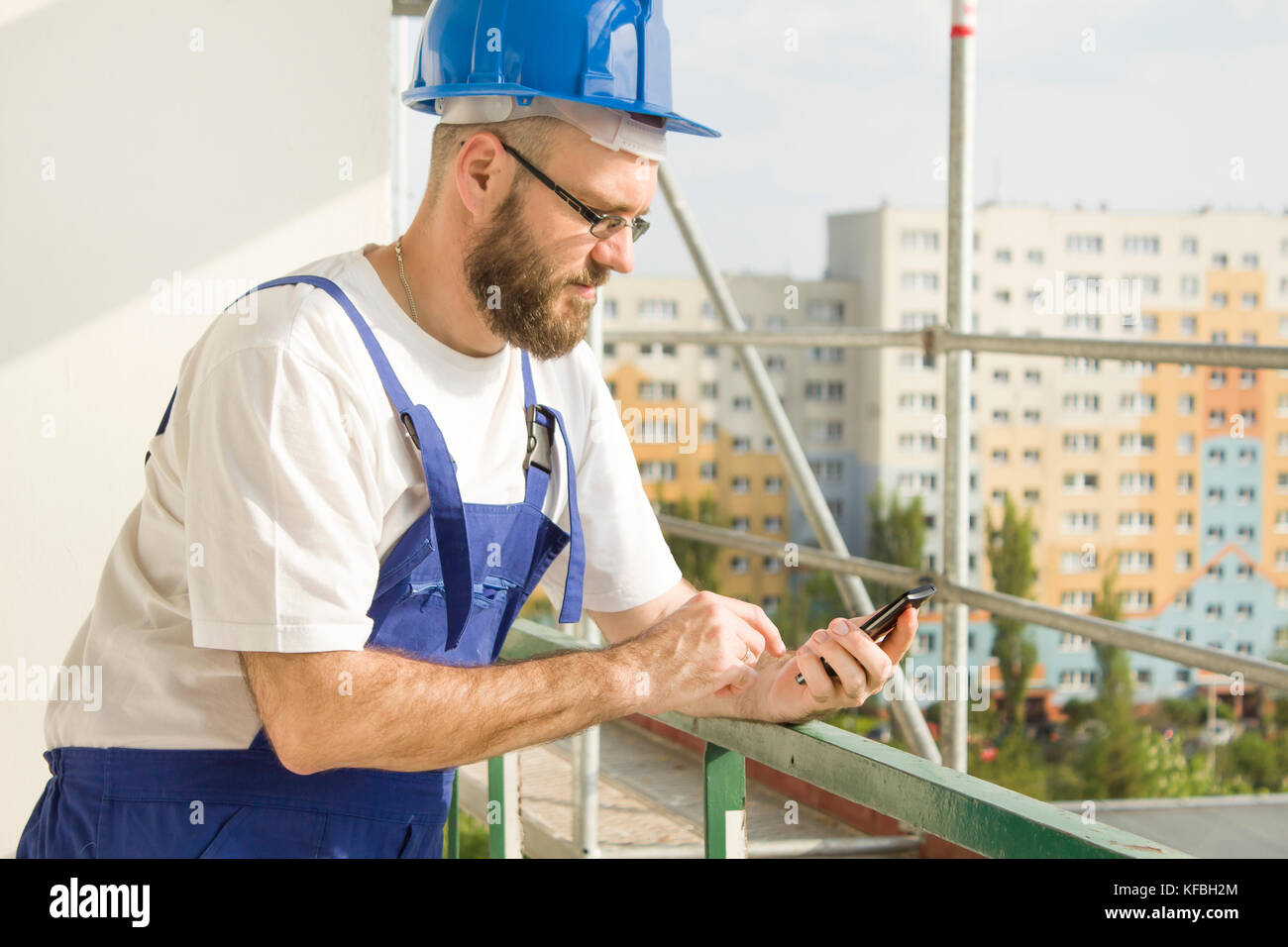 construction worker in work wear and a helmet holding a mobile phone in his hand and dialing a number. Work at high - Stock Image