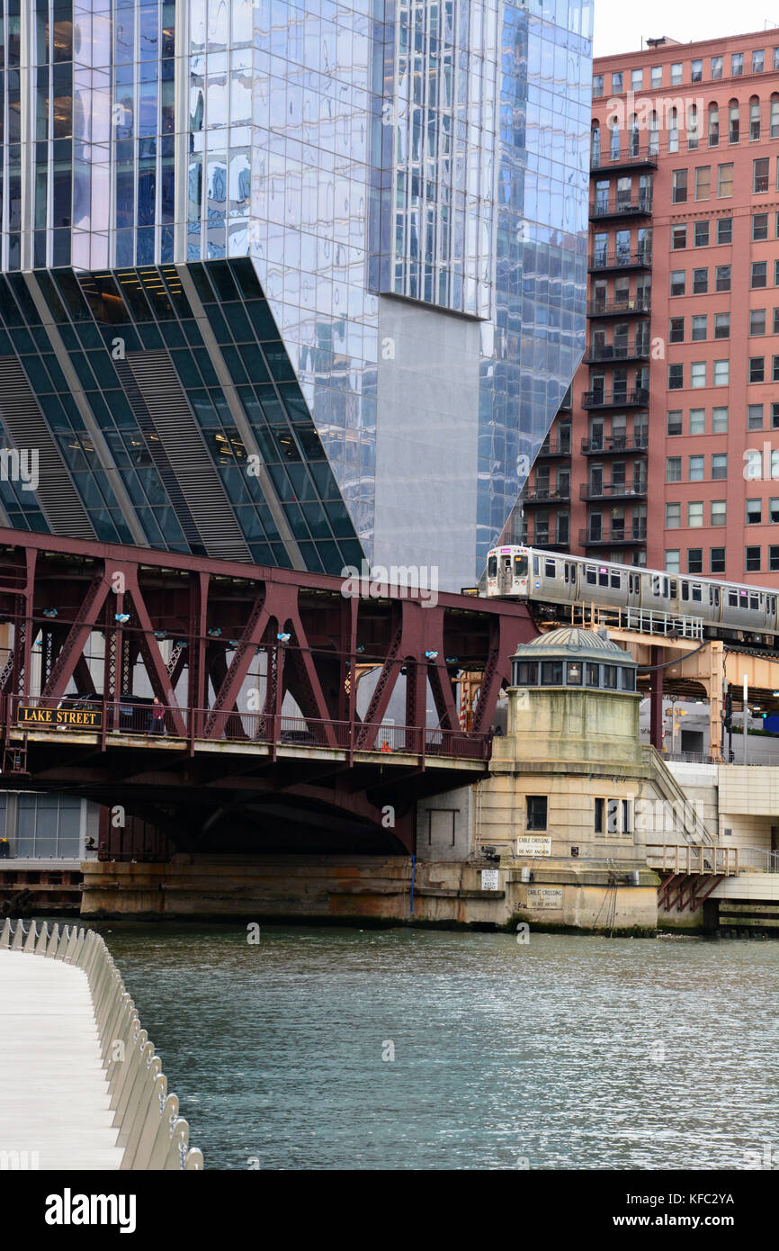 A pink line L train crosses the Chicago River at Lake Street in front of the cantilevered skyscraper at 150 N Riverside Stock Photo