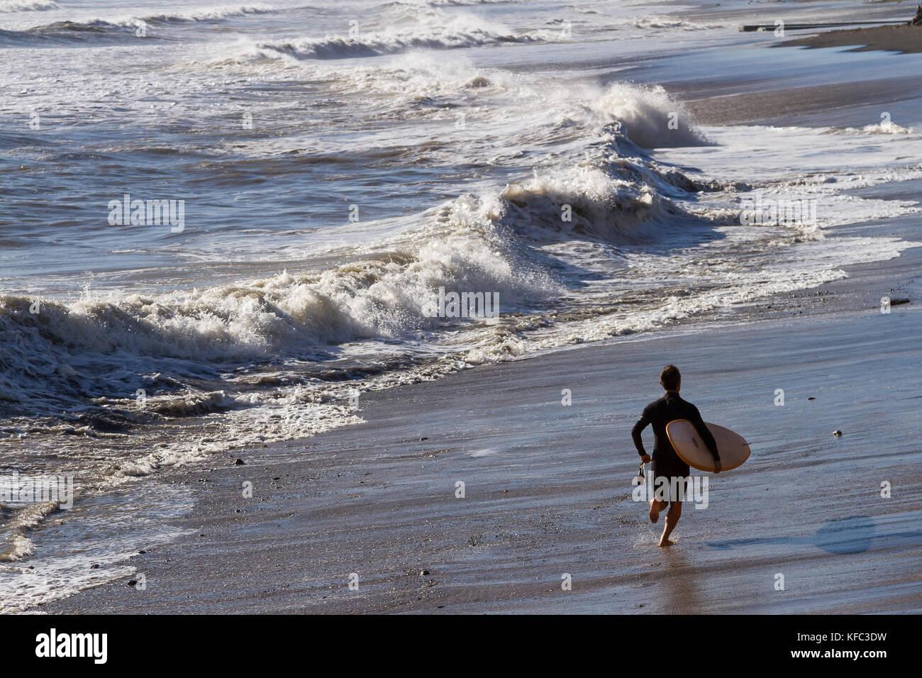 A surfer runs along the beach in Enoshima, Kanagawa, Japan. Monday October 23rd 2017 - Stock Image
