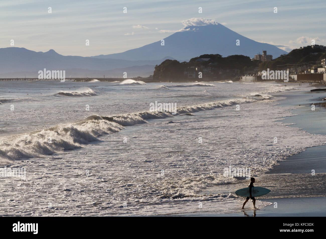 A surfer on the beach with Mount Fuji behind. Enoshima, Kanagawa, Japan. Monday October 23rd 2017 - Stock Image