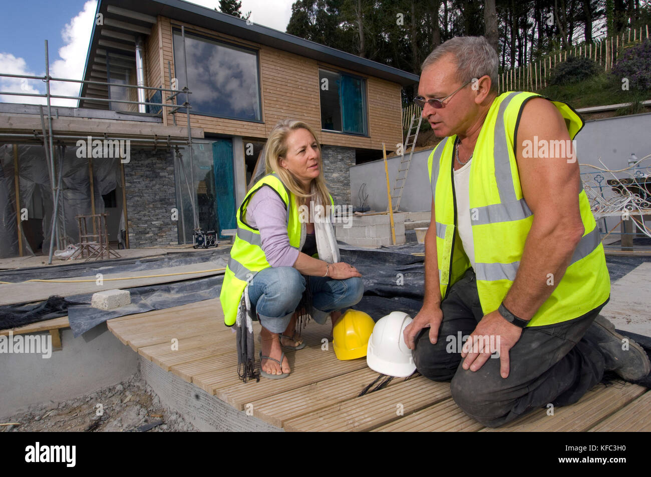 Interior and building designer Claire Alderson (red top, overseeing work on a property in Cornwall - Stock Image