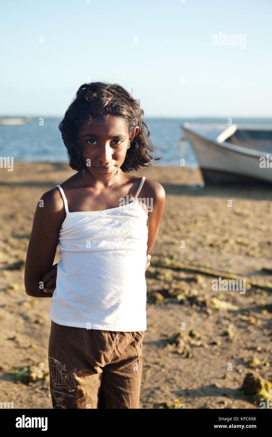 MAURITIUS, a young girl walks on the beach by a fishing boat in Bel Ombre - Stock Image
