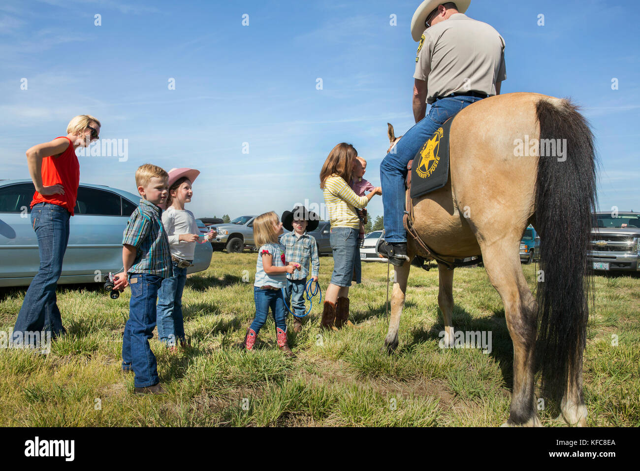 USA, Oregon, Sisters, Sisters Rodeo, young kids meet and pet the Sheriff's horse - Stock Image