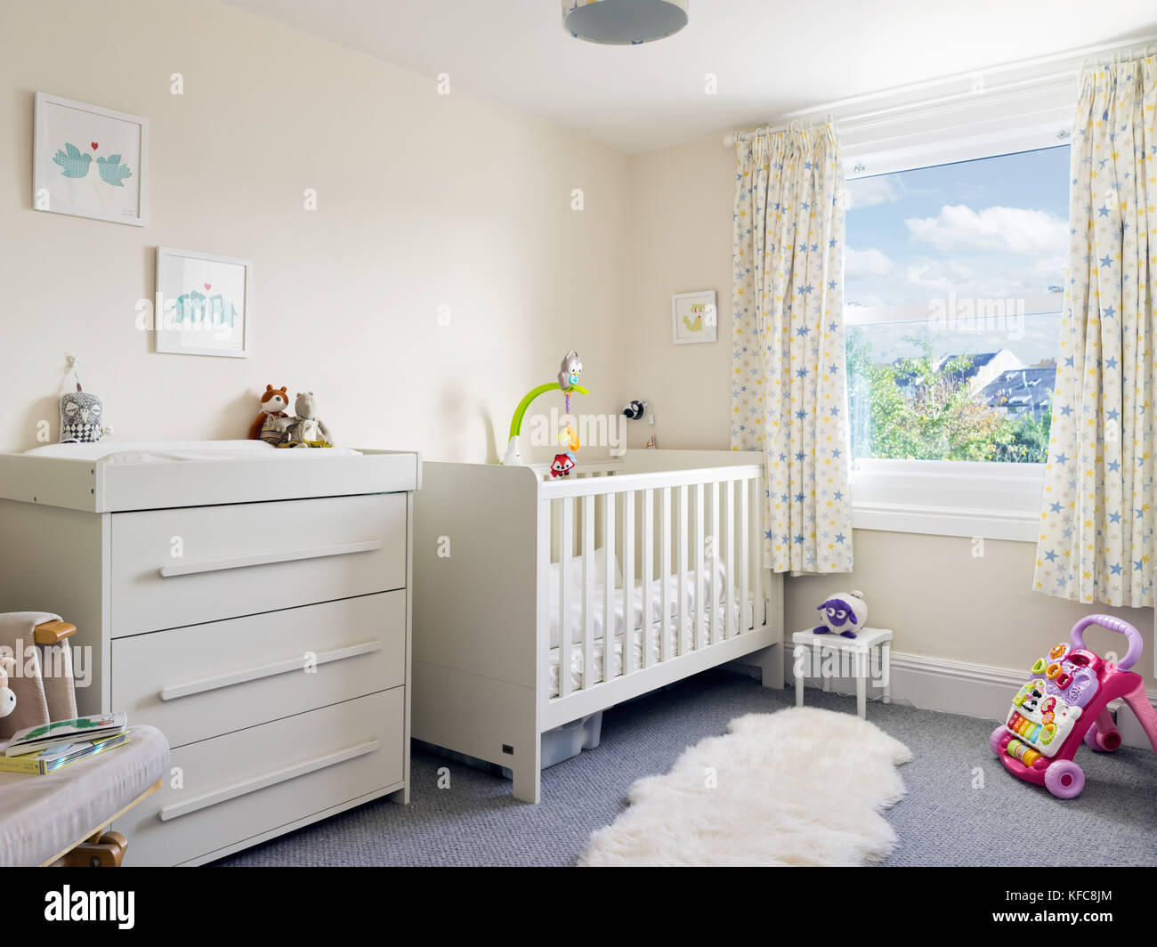 A modern, clean & tidy child's nursery room decorated in a contemporary style including a cot & changing - Stock Image