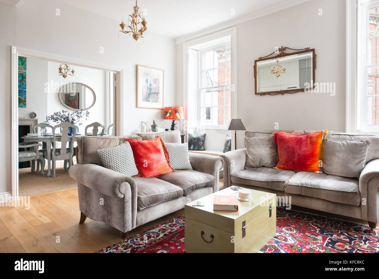 A contemporary / traditionally styled domestic living room with a view through to a stylish dining room in a UK - Stock Image