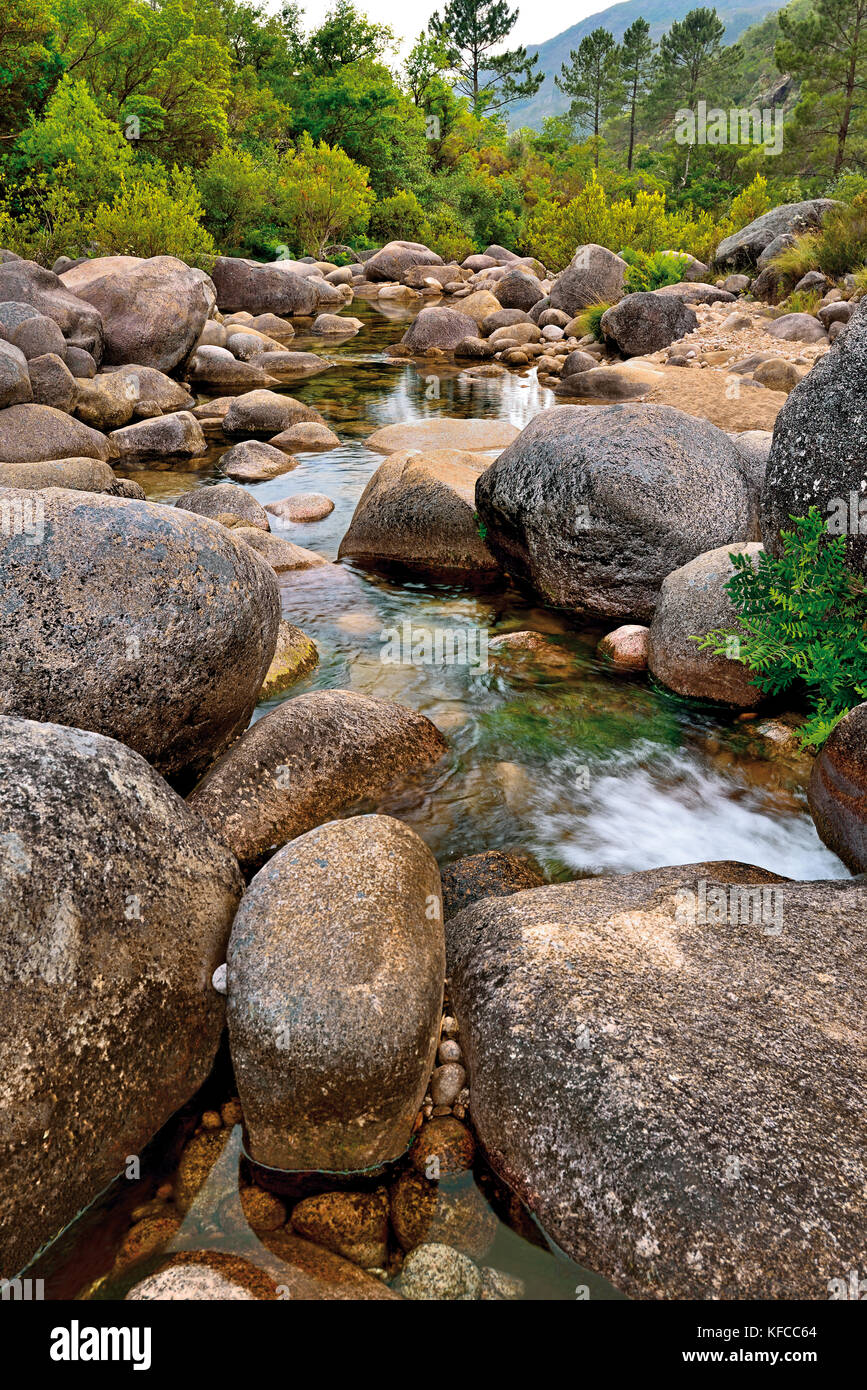 Huge rocks and transparent waters of a mountain river surrounded by green hills and valleys - Stock Image